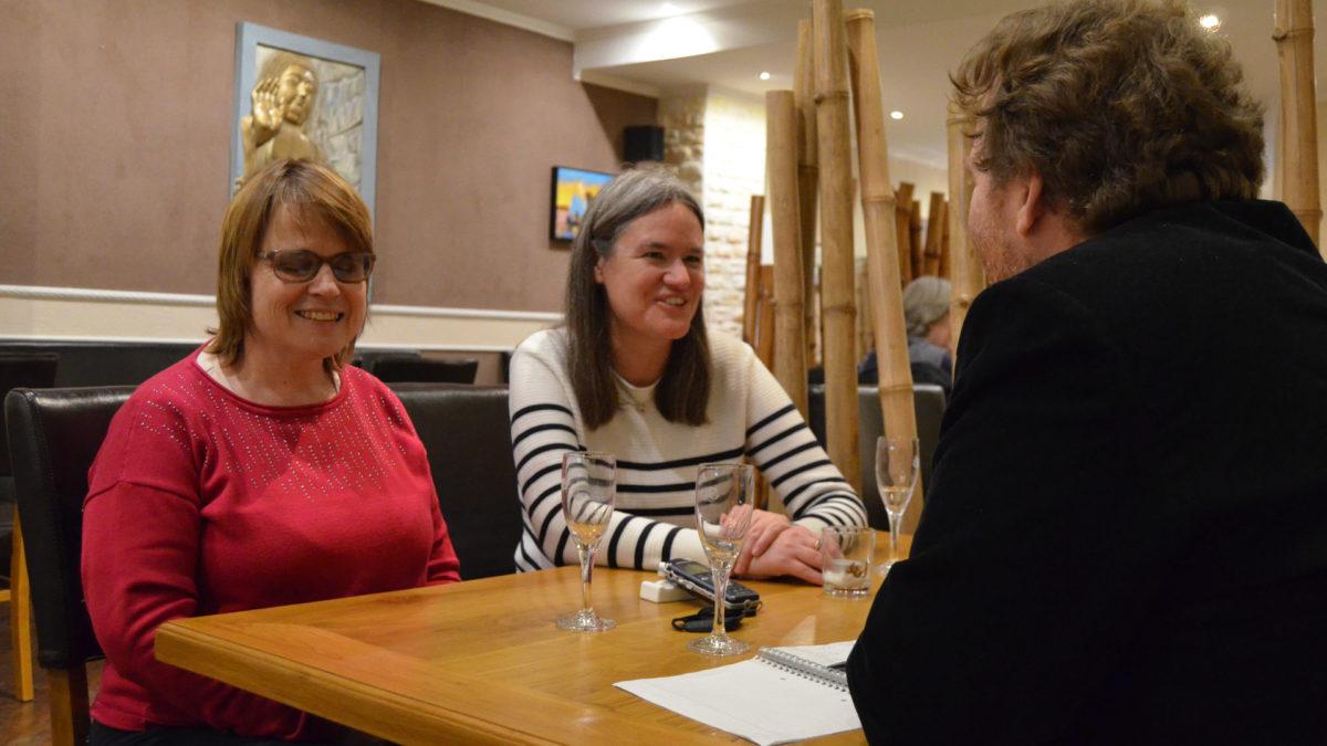 """Drei Personen sitzen an einem Tisch in einem Restaurant. Am Tisch sitzen von links nach rechts Nina Schweppe und Regina Hillmann, die Vorsitzenden des Fanclubs """"Sehhunde"""". Im Vordergrund mit dem Rücken zum Betrachter gewandt sitzt Florian Reinecke, der das Interview führte."""