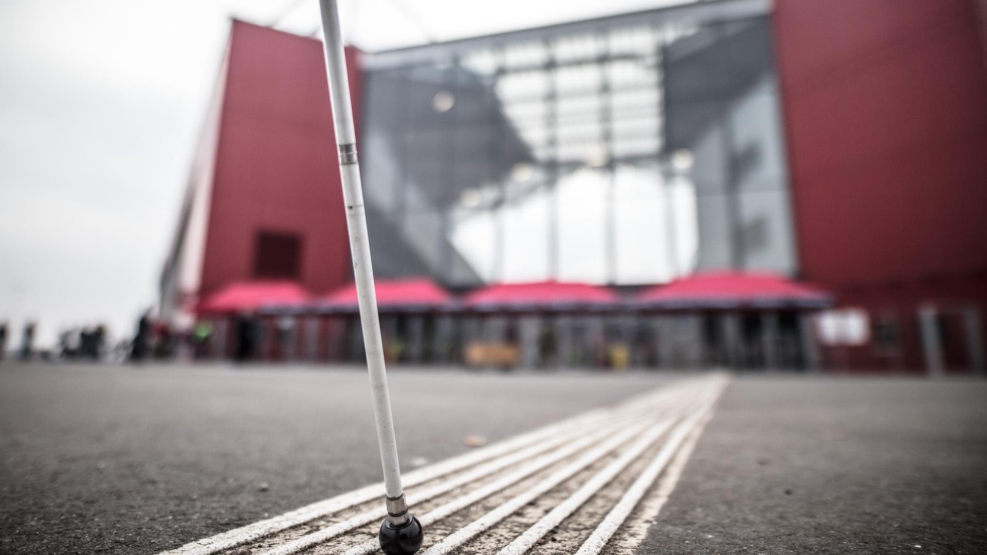 Ein Pendel- beziehungsweise Blindenstock wird von einer Person in der Mitte eines taktilen Führungssystems (Blindenleitsystems) geführt. Dieses führt direkt auf die Mainzer OPEL ARENA zu, die im Hintergrund leicht unscharf zu erkennen ist.