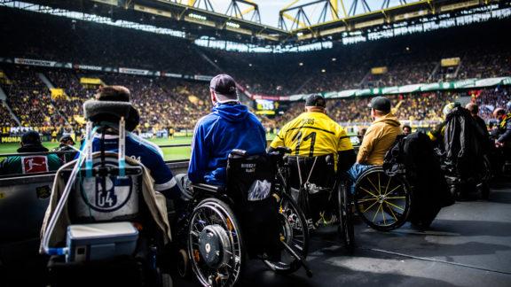 Fans des FC Schalke 04 und von Borussia Dortmund, zu erkennen an den jeweiligen Trikots, verfolgen im Rollstuhl sitzend ein Bundesliga-Spiel im Dortmunder SIGNAL IDUNA PARK. Im hinteren Teil des Bildes sind Tribünen des SIGNAL IDUNA PARK und die einprägsame schwarz-gelbe Dachkonstruktion gut zu erkennen.