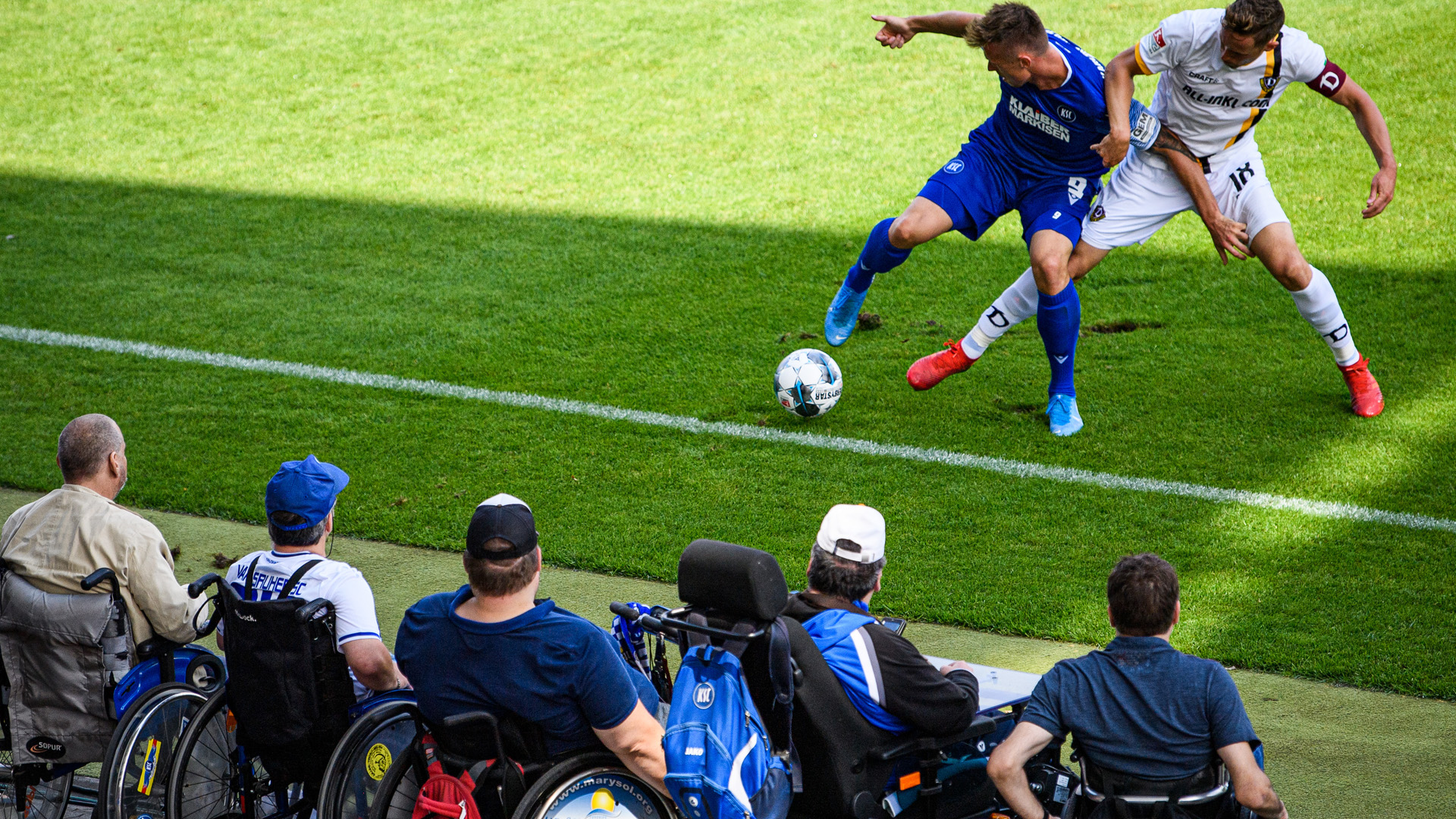 Fans im Rollstuhl verfolgen im Karlsruher Wildparkstadion am Spielfeldrand sitzend einen Zweikampf zwischen KSC- Spieler Marvin Pourie und dem Spieler Jannik Müller von der SG Dynamo Dresden, der die Kapitänsbinde trägt.