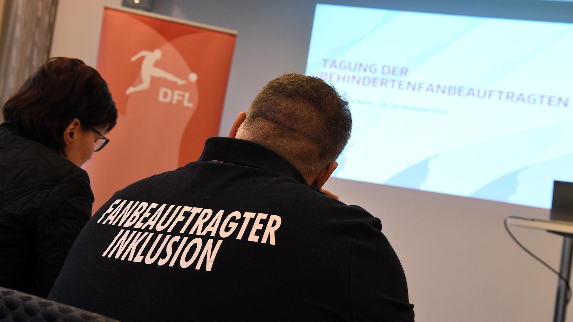 """Auf dem Foto sind zwei Personen mit dem Rücken zum Betrachter gerichtet im Vordergrund zu sehen. Auf einem T-Shirt steht """"Fanbeauftragter Inklusion"""". Im Hintergrund sind ein roter Aufsteller mit weißem DFL-Logo und eine Wandprojektion mit der Aufschrift """"Tagung der Behindertenfanbeauftragten"""" zu sehen."""