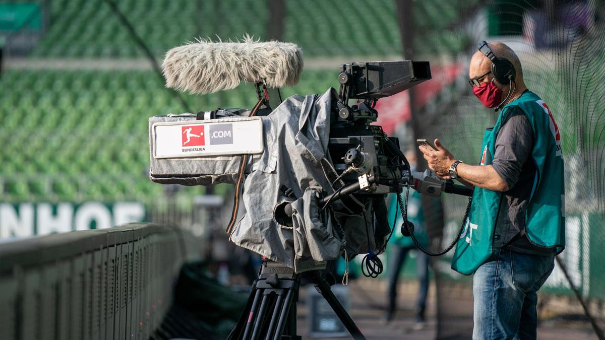 Eine Kamera mit Bundesliga-Logo im leeren Stadion, ein Kameramann steht dahinter.