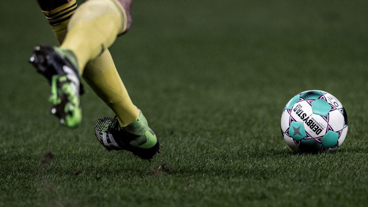 Spielszene: Unterschenkel eines Spielers und Derbystar Matchball auf dem Platz