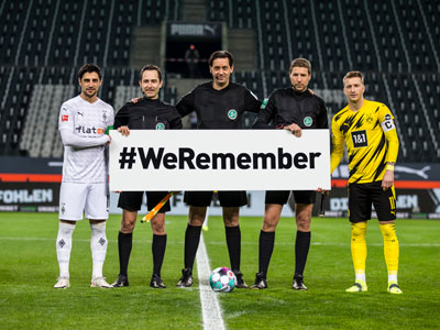"""Spieler von Borussia Mönchengladbach und Borussia Dortmund sowie Schiedsrichter halten ein Schild hoch mit dem Schriftzug """"#WeRemember"""""""