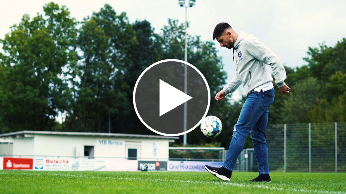 Malik Batmaz ist auf einem Rasensportplatz von der Seite zu sehen und jongliert einen Ball kickend in der Luft