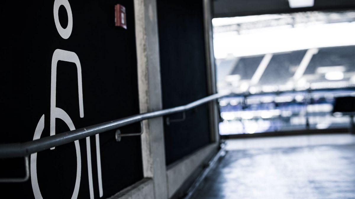 Gang zur Stadiontribüne, an der Wand ist ein Rollstuhl-Symbol aufgemalt