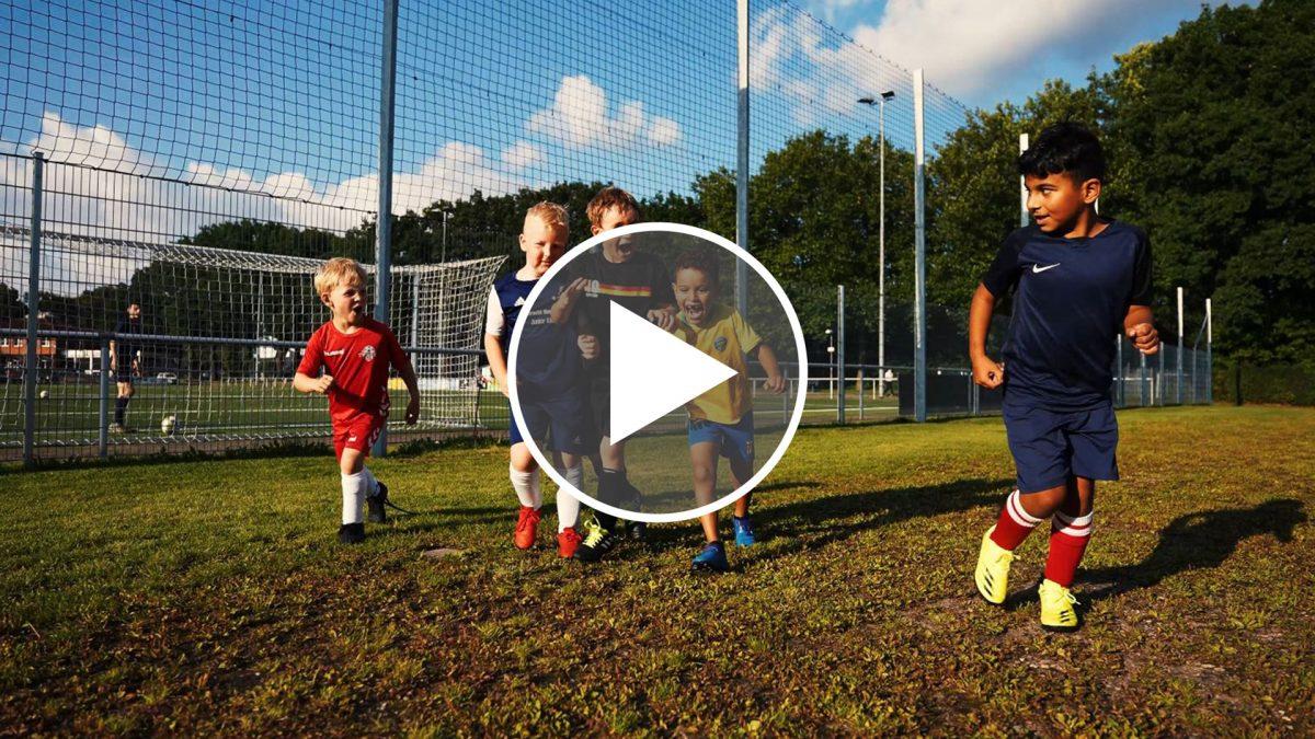 Kleine Jungs rennen über den Rasenballsportplatz.