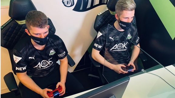 Two players of Borussia Mönchengladbach playing with console controllers